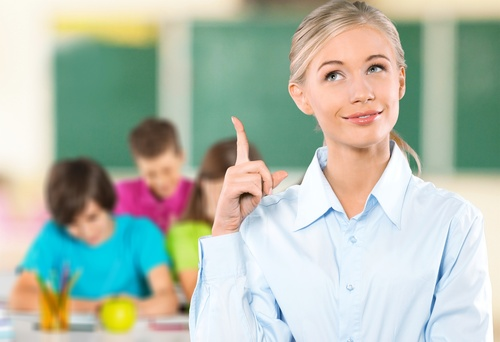 teacher in classroom holding up index finger, she has an idea