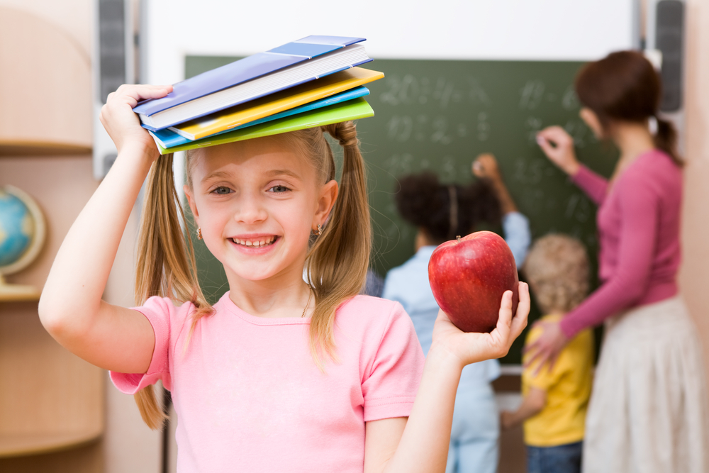 A girl student holding books on her head with an apple in the other hand