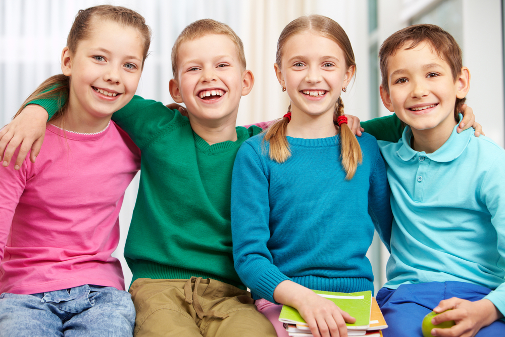 Four school age kids standing arm and arm smiling