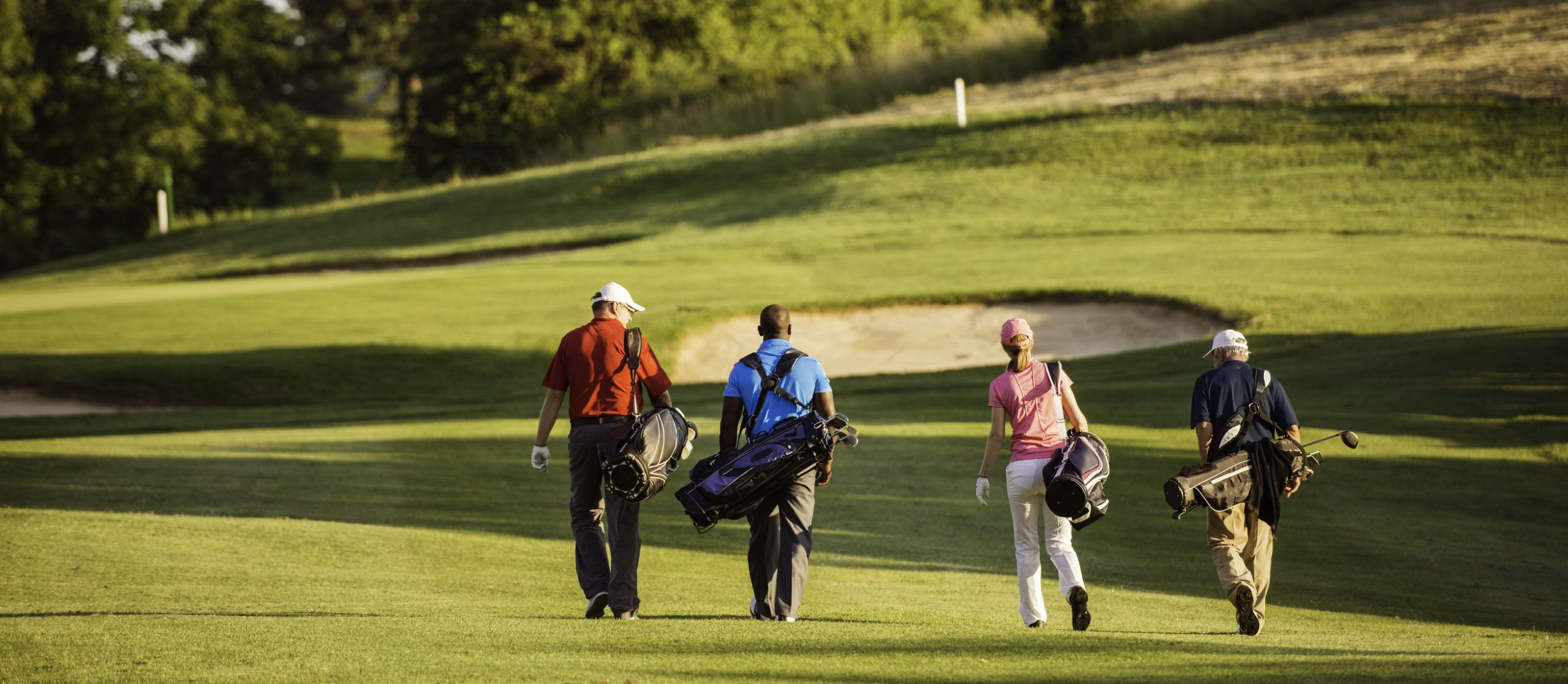 Golfers walking on fairway
