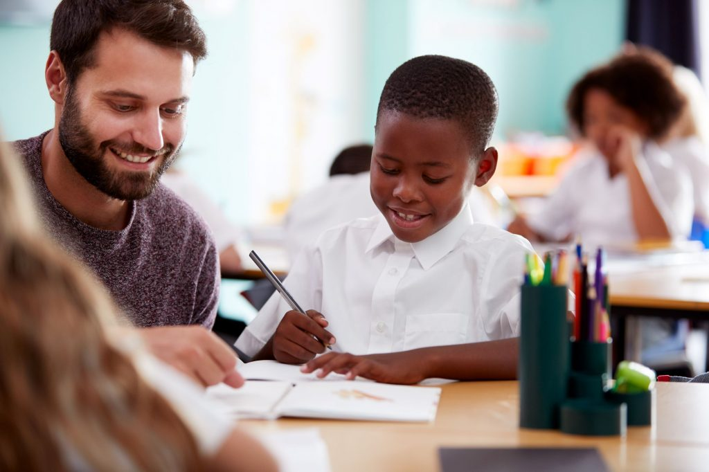Male teacher working with African American student