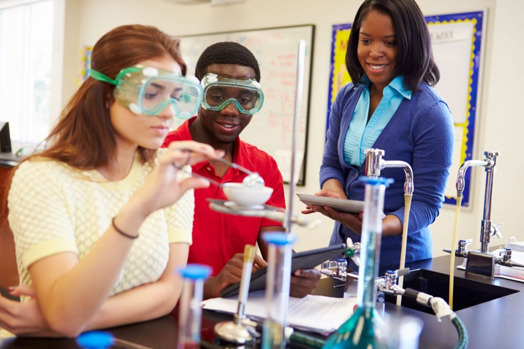Female teacher directing two students doing an experiment